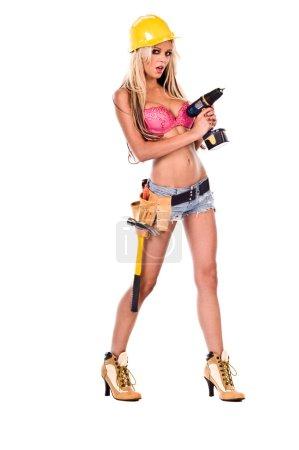 Photo pour Haute couture glamour modèle iin titito duc Short, ceinture porte-outils, soutien-gorge rose et jaune un casque avec une visseuse et des bottes à talons hauts - image libre de droit