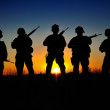 Silhouettes of the American marines against a risi...