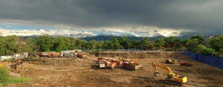 Photo pour Panorama cousu. Les voitures sortent un terrain d'un fossé de fondation de bâtiment. Un panorama contre les montagnes et le ciel orageux . - image libre de droit