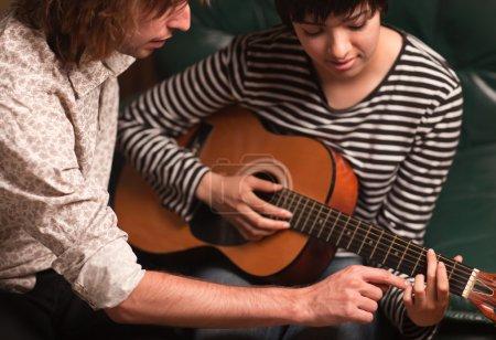 Photo pour Un jeune musicien enseigne à une étudiante comment jouer de la guitare . - image libre de droit