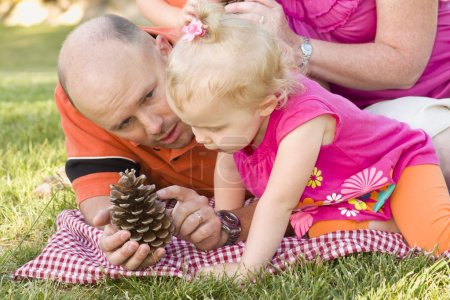 Father and Daughter Talk about Pine Cone in Park