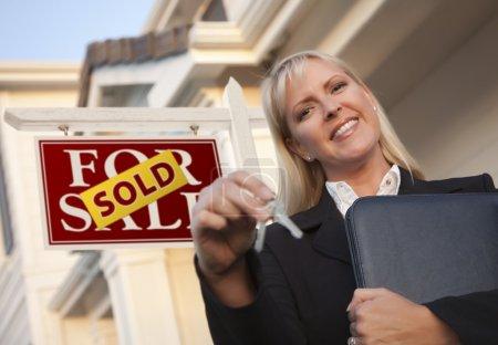 Photo pour Agent immobilier femelle avec touches devant sign. - image libre de droit