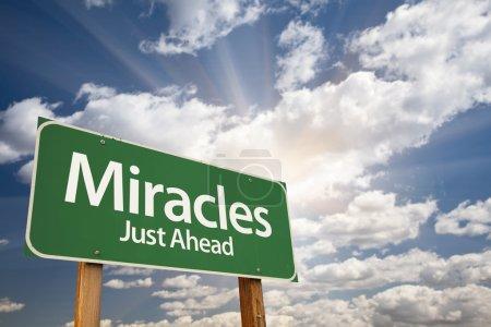 Photo pour Miracles Green Road signe contre les nuages et les coups de soleil . - image libre de droit
