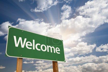 Photo pour Panneau Bienvenue vert contre les nuages et sunburst. - image libre de droit