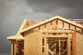 Home Construction Framing with Ominous Clouds