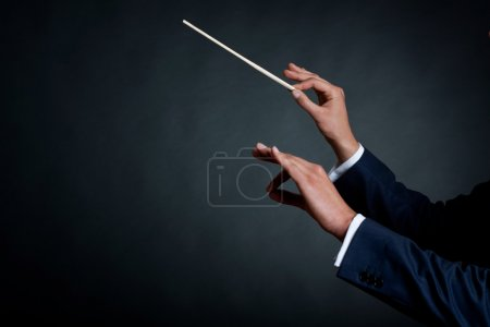 Photo for Image of a male orchestra conductor directing with his baton in concert - Royalty Free Image