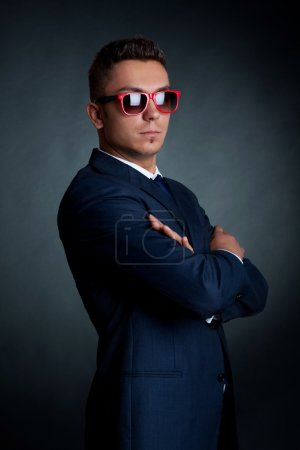 Photo for Confident fashion business man in red sunglasses standing with hands crossed - Royalty Free Image