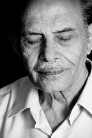 Photo pour Un portrait d'un homme senior asiatique avec ses yeux fermés. monochrome. - image libre de droit