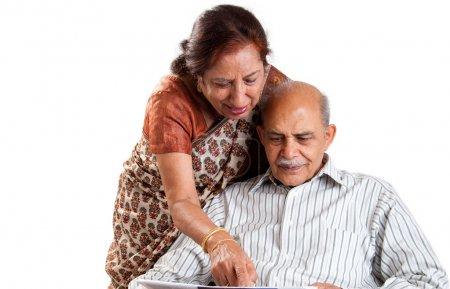Photo pour Un couple de personnes âgées indienne / asiatique pointant sur un journal - isolé sur blanc - image libre de droit