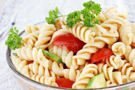 Photo pour Salade de pâtes avec vinaigrette, tomates fraîches, concombres et le persil. faible profondeur de champ. - image libre de droit