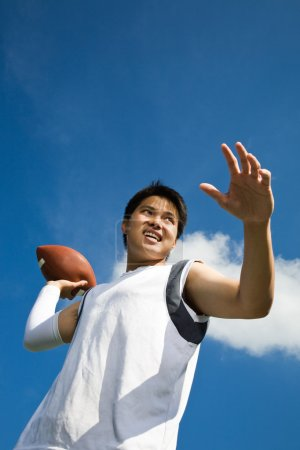 Photo for A young asian football player throwing a football - Royalty Free Image