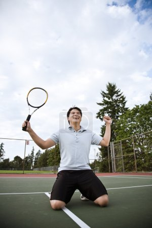 Asian tennis player in joy after winning