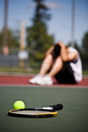 Photo for A sad male tennis player sitting down in disappointment after defeat - Royalty Free Image