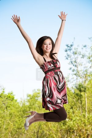 Photo for A beautiful asian woman jumping for joy - Royalty Free Image