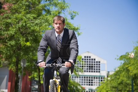 Caucasian businessman riding a bicycle
