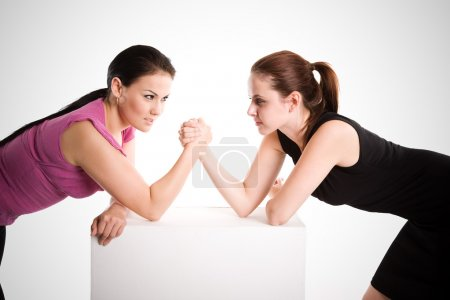 Two businesswomen arm wrestling