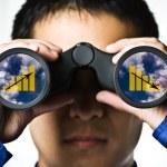 A businessman looking through binoculars, seeing c...