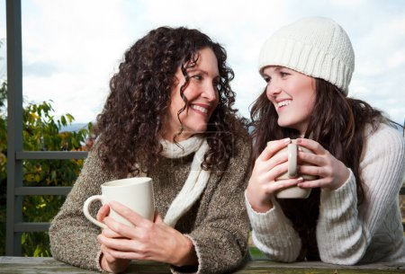 Photo for A portrait of a happy mother and daughter drinking coffee outdoor - Royalty Free Image