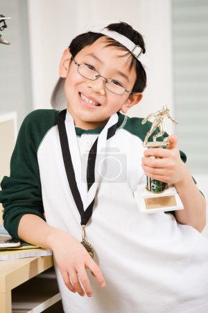 Photo for An asian boy showing his winning sport medal and trophy - Royalty Free Image