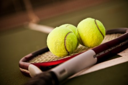 A shot of a tennis racquet and tennis balls on the...