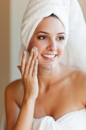 Photo pour Une photo d'une jeune femme belle application de lotion pour le visage - image libre de droit