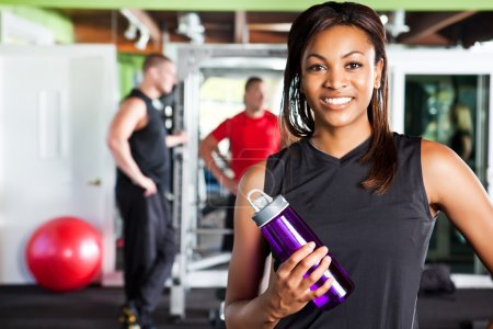 Photo for A shot of a happy black female athlete holding a water bottle in a gym - Royalty Free Image