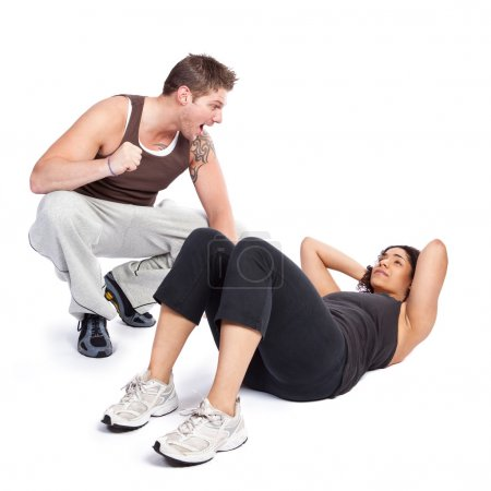 Photo for A woman doing situps with her personal trainer - Royalty Free Image