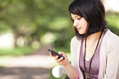 Photo for A shot of a mixed race girl texting on the phone at campus - Royalty Free Image