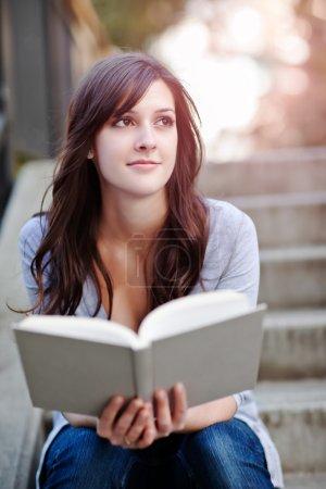 Photo pour Une photo d'un étudiant souriant lisant un livre - image libre de droit
