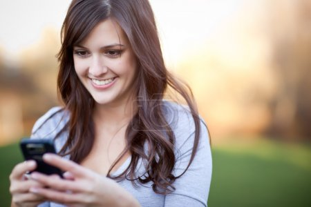 Photo for A portrait of a smiling beautiful woman texting with her phone - Royalty Free Image