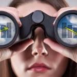 A businesswoman looking through binoculars, seeing...