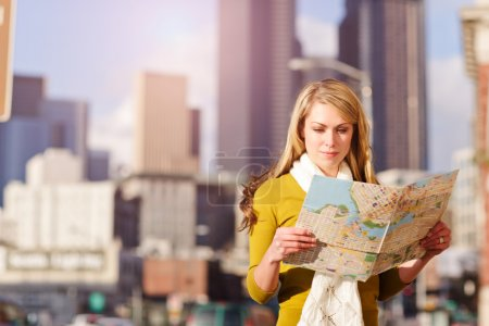 Photo for A shot of a beautiful caucasian traveling woman reading a map - Royalty Free Image