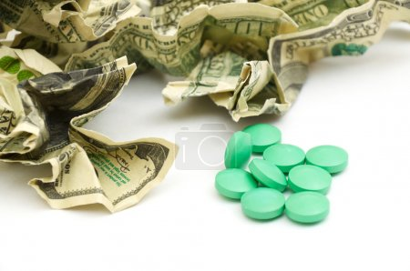 Crumpled american money and pills