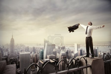 Photo for Happy businessman standing on the rooftop of a skyscraper - Royalty Free Image