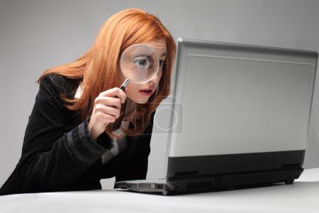 Photo pour Jeune femme d'affaires, observant un ordinateur portable à la loupe - image libre de droit