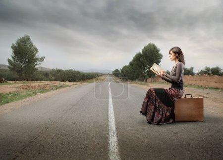Photo pour Belle femme assise sur une valise sur une route de campagne et lisant un livre - image libre de droit