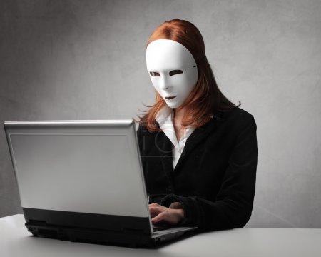 Photo pour Femme d'affaires masquée utilisant un ordinateur portable - image libre de droit