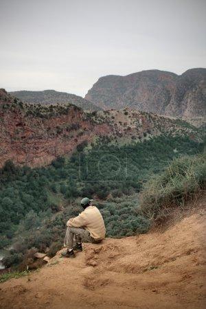 Photo pour Homme assis sur une clairière, sur un pays montagneux - image libre de droit