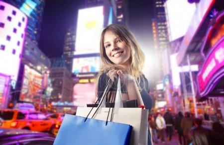 Photo pour Belle femme portant plusieurs sacs à provisions avec le paysage urbain de nuit en arrière-plan - image libre de droit