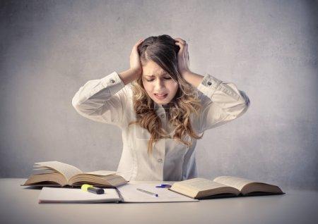 Photo pour Belle étudiante souffrant de maux de tête pendant ses études - image libre de droit