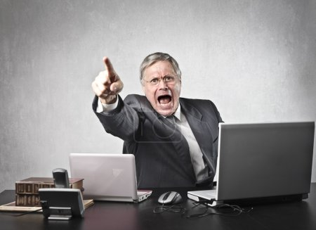 Photo for Angry senior businessman sitting at his desk and screaming - Royalty Free Image