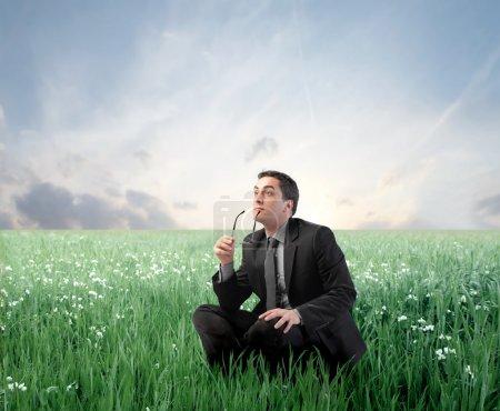 Photo pour Homme d'affaires avec expression pensive, assis sur un pré vert - image libre de droit