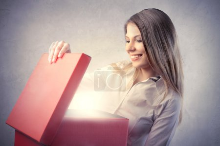 Photo for Smiling beautiful woman opening a present - Royalty Free Image