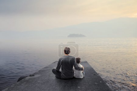 Father and son sitting on a pier over a lake...