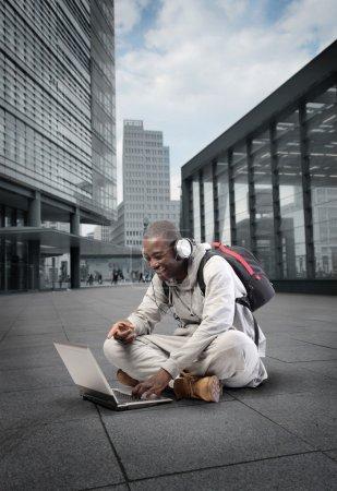 Photo pour Rire le jeune homme assis sur une rue de la ville et à l'aide d'un ordinateur portable - image libre de droit
