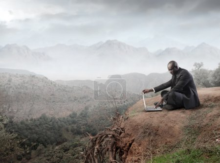 African businessman sitting on a rock and using a laptop