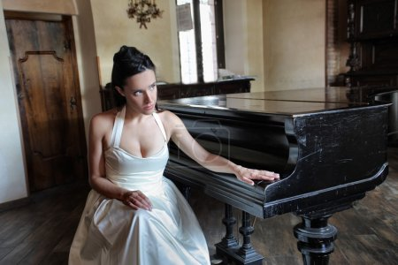 Photo for Beautiful bride sitting beside a piano - Royalty Free Image