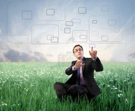 Photo pour Homme d'affaires assis sur une prairie verte et appuyant sur des boutons sur un écran tactile - image libre de droit