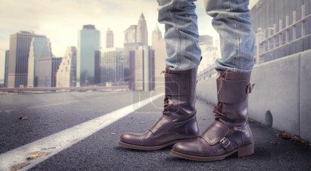 Photo pour Gros plan des pieds de l'homme portant des bottes de mode avec le paysage urbain en arrière-plan - image libre de droit
