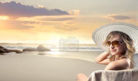 Photo pour Belle femme assise sur un transat au bord de la mer - image libre de droit